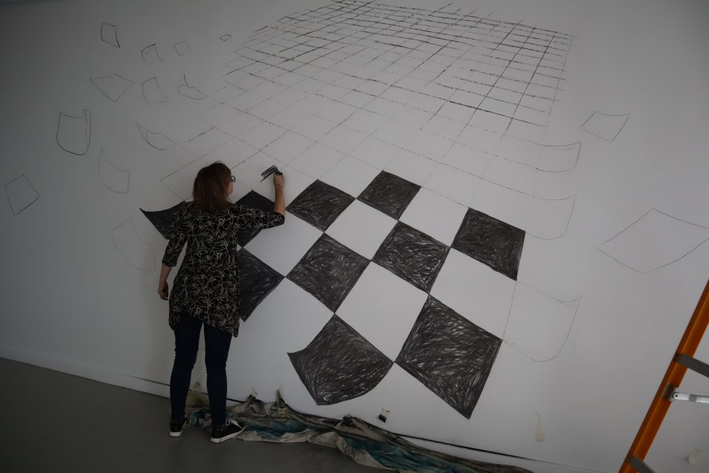 Shana JAmes in the process of drawing on the Gallery Wall